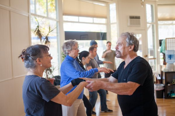 Teacher helping student with a tai chi posture