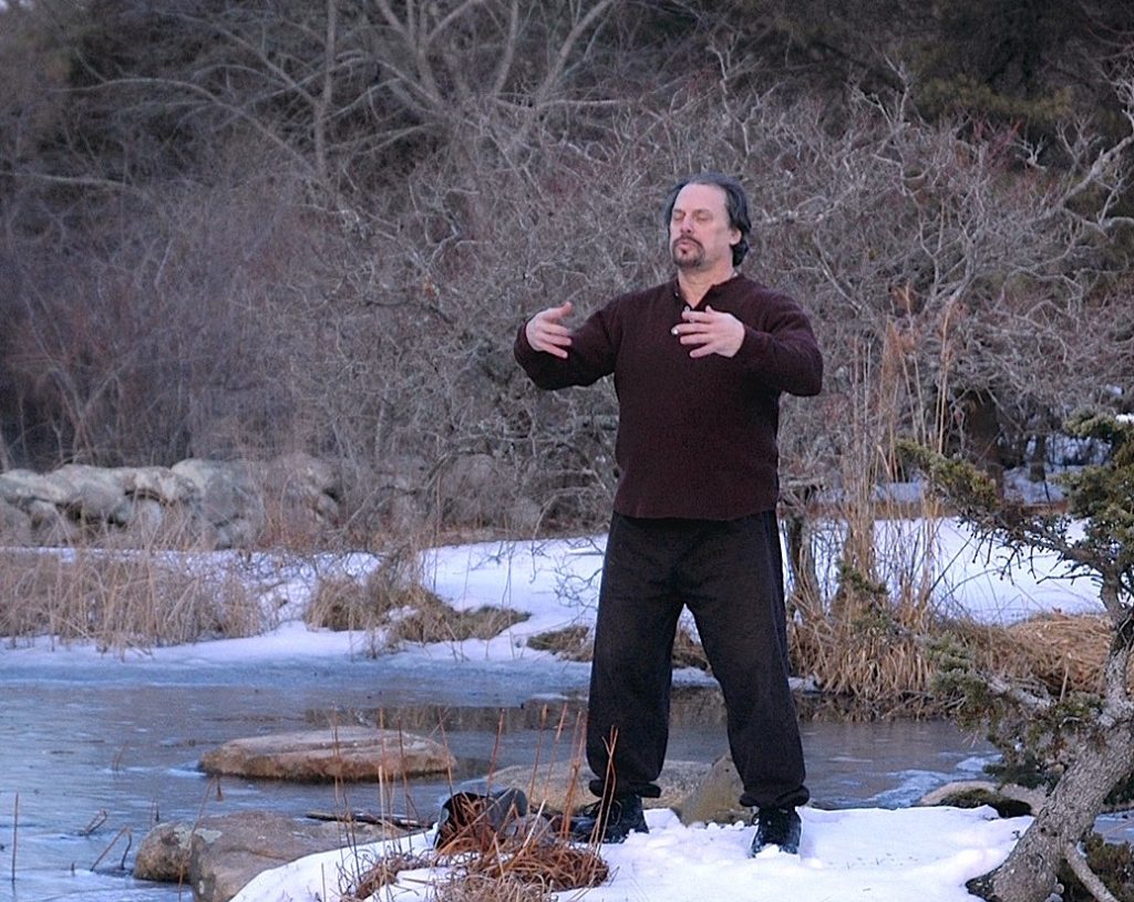 A man standing outdoors on the snow practicing Tai Chi
