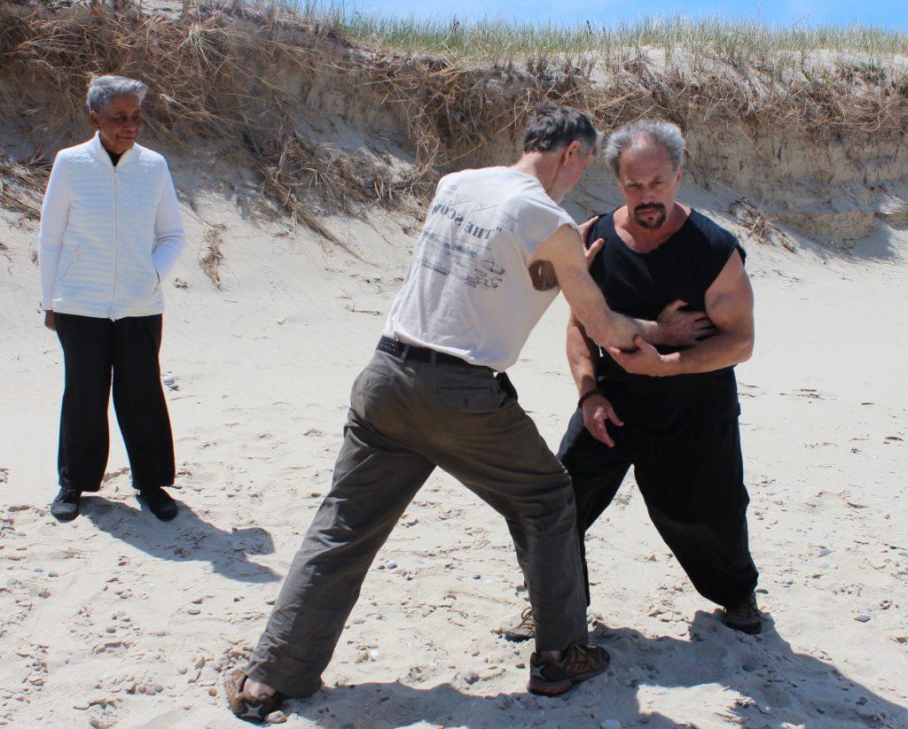 Men practicing Tai Chi push hands outdoors