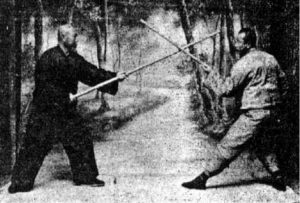 Two Martial Artists Fighting with Wooden Staffs